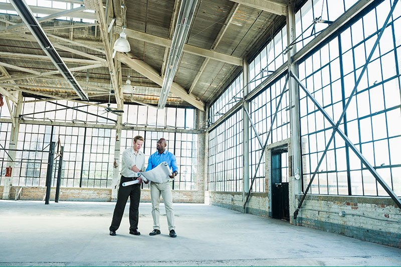 two men standing in warehouse with blueprints